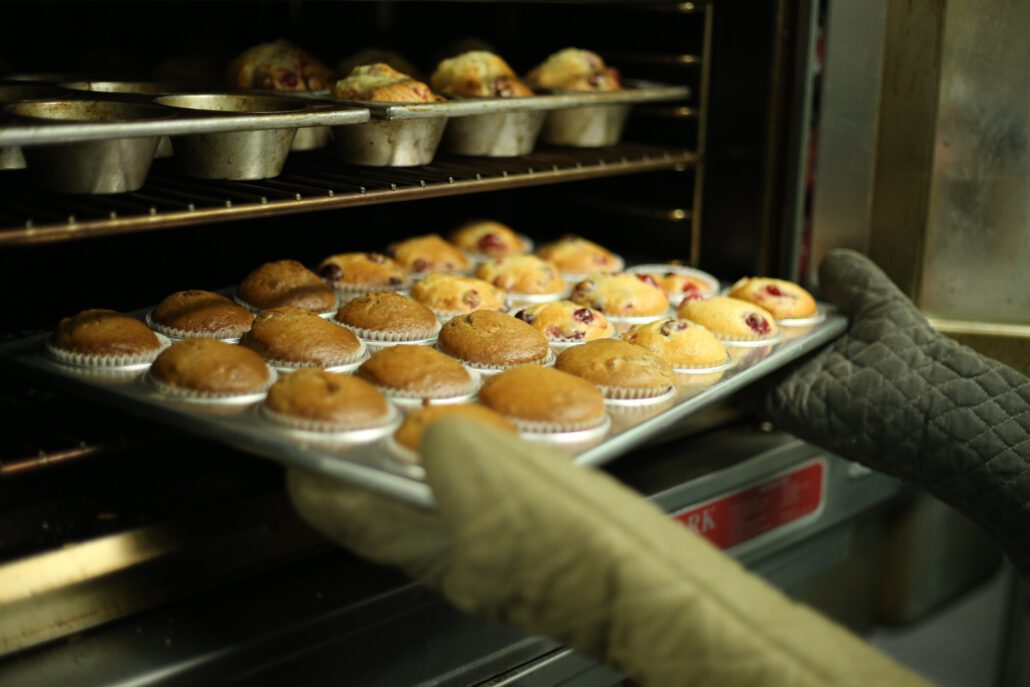 Tray of muffins coming out of an industrial oven