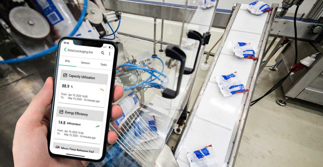 Packaging production line with hand holding mobile device showing innius Insight app
